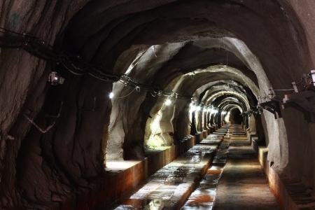long walk way in dark tunnel with light