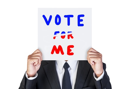 Businessman holding paper that say vote for me