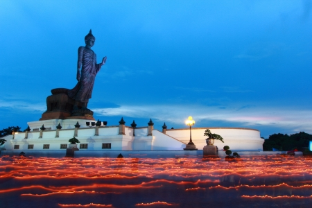 People walks with lighted candles in hand around buddha image photo