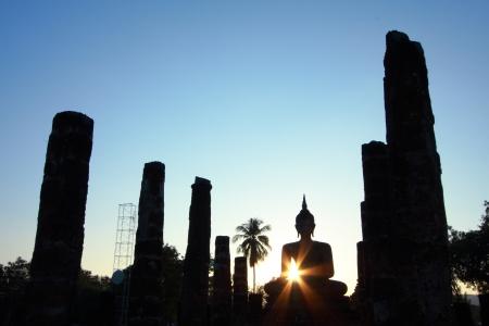 hunker: Silhouette buddha image at Sukhothai Historical Park, Thailand
