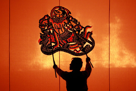 RATCHBURI, THAILAND - APRIL 13: Large Shadow Play is performed at Wat Khanon on April 13, 2013. The ancient performing art involves manipulating puppets of cowhide in front of a backlit white screen