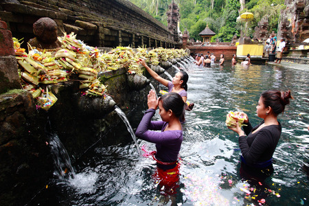 pura: BALI, INDONESIA - MAY 6: Worshippers make an offering at the Tirta Empul Temple on May 6, 2013 in Bali, Indonesia. They believe that water from the spring is holy and has the healing power.