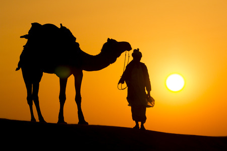 A desert local walks lead nose camel through Thar Desert dramatic sun background photo