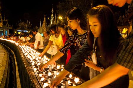 YANGON, MYANMAR - FEBRUARY 13: Buddhist devotees lighting candles at the Shwedagon Pagoda on Feb 13, 2011 in Yangon, Myanmar (Burma).