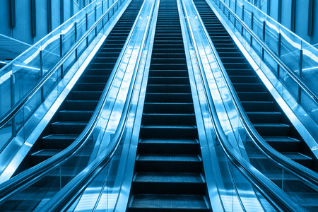 two tone: escalator blue two tone color going up stair in building  Stock Photo