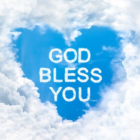 神は心の雲の形態の中の青い空上の単語を祝福します。 写真素材