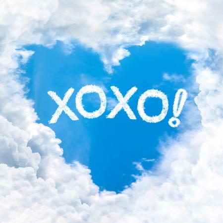 xoxo: xoxo or kiss and hug word on blue sky inside heart cloud form