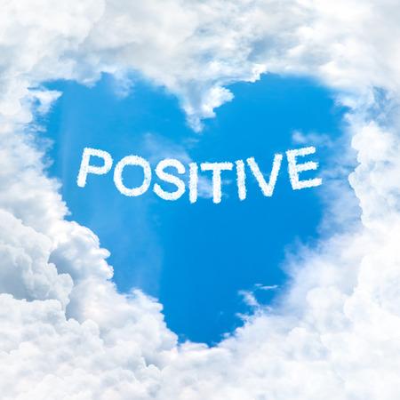 positive word on blue sky inside love heart cloud form photo