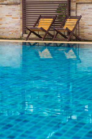 Chair on ground beside swimming pool day time with nobody photo