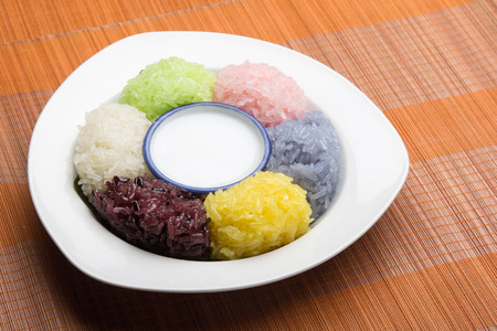 thai dessert: dessert sweet sticky rice with coconut milk in plate on wood pattern background Stock Photo