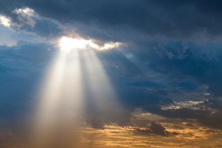 일몰 시간 동안 비 구름에서 내려 오는 태양 광선 빛