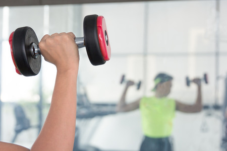 chrome man: A young man watches arm muscle standing in front of the mirror as he performs a bicep curl with a chrome dumbbell