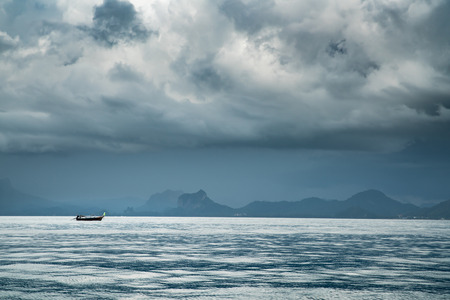 storm coming: small boat on the sea during storm coming with dark cloud.