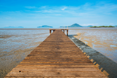 Wood bridge over land extends into the sea during ebb tide time with blue sky background