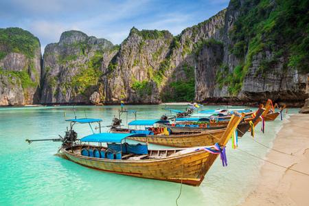 Thailand sea beach view round with steep limestone hills with many traditional longtail boats parking at Maya Bay, Ko Phi Phi Leh island, part of Krabi, Andaman Sea