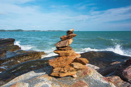 sea beach stone stack stable and wave splash abstract and blue sky background