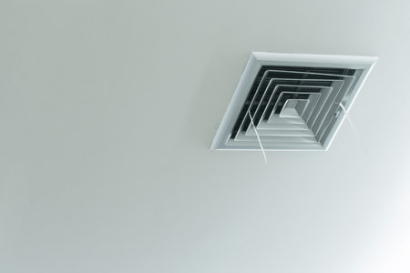 Grille of air conditioner system over head under ceiling.
