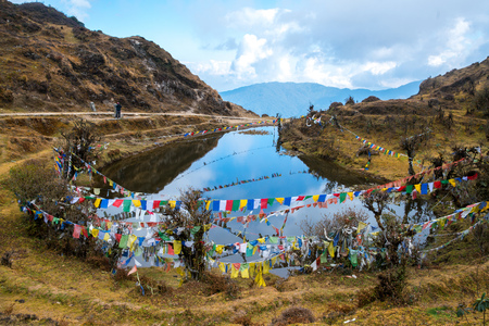 Tibetan prayer flag or Lung ta and beside pond, the flag hang on high place for wind flow wish of people all around , Sikkim, India Stock fotó - 89478524