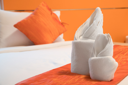 Towel Origami prepared on a bed in orange color room