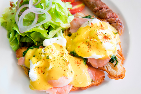 Egg benedict with smoked salmon, sauce, green salad vegetable and grill hot dog Stock Photo