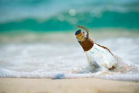 Letter message in a glass transparent bottle on the beach , concept for communication.