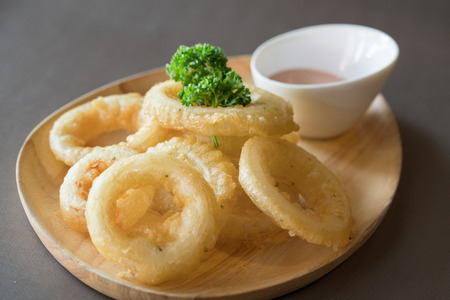 fried onion rings in batter with sauce on wood table
