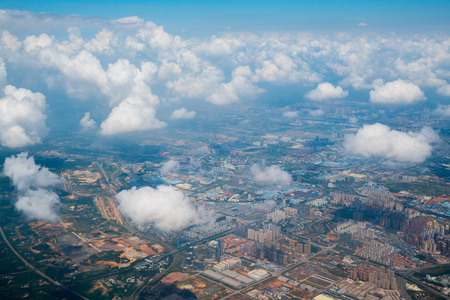 aerial view, flying above the puffy white clouds and over ground landscape in China, Asia.