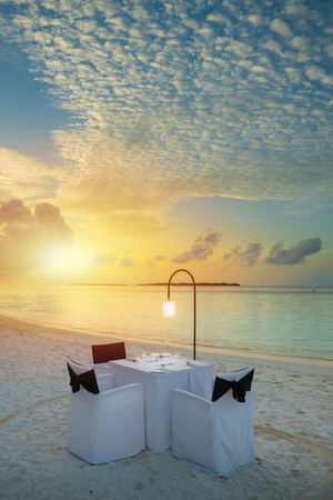 Table outdoor next to sea scenic prepare for special romantic dinner time with sunlight shading 版權商用圖片