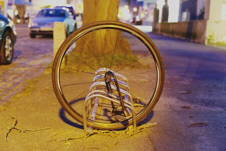 Abandoned bicycle wheel of a stolen bicycle, chain from front wheel.