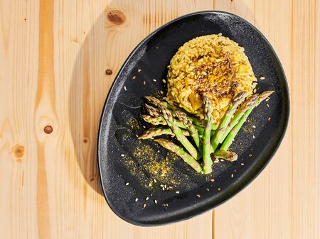 Vegan curry risotto with fresh green asparagus, olive oli and linseed, served on a black plate, no butter, no animal fat