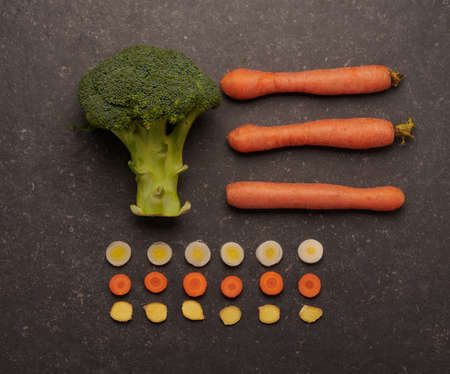 Fresh and raw broccoli and carrots, with leek and ginger cut into rounds, in a schematic composition, on a dark stone background.