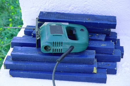 Cut blue wooden slats and wood cutting saw, left in the yard Stock Photo
