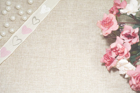 Roses, pearls and decorative band with hearts on the jute background. A bouquet of roses, pearls and a heart from a wicker on jute