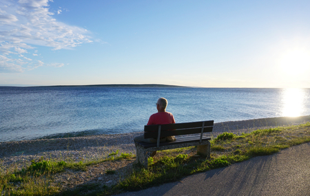 Mandre, Island of Pag, Croatia, Jun 22, 2018. Old man sitting on the bench by the blue sea and looking in the distance at sunset