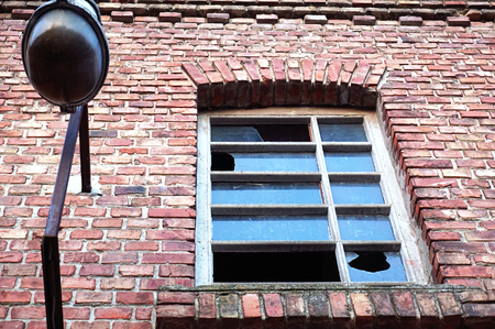 Details on industrial building ruin made of red brick, lamp and window with broken glass, abandoned and destroyed industrial building