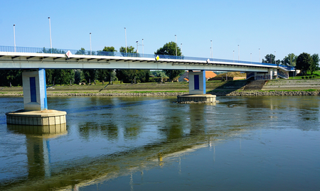 River bridge across Drava river and reflection of bridge in river water, on sunny summer day in Croatian town Osijek, waterfront view Stock Photo