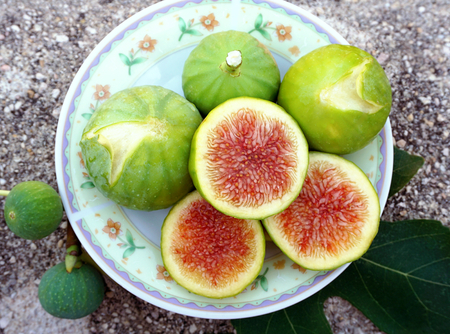 Ficus domestica, domestic orgabic green figs on small plate, flat lay, sliced and whole, top view