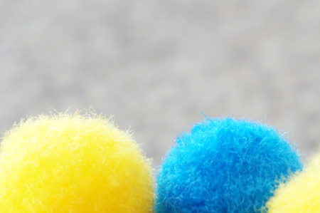 Two wool pom poms close up view on a gray background with free space for text