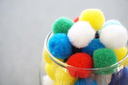 Multicolor wool balls pom poms in glass. Funny and vivid background concept Stock Photo