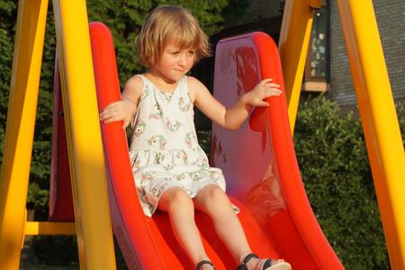 Petite fille de 6 ans sur le toboggan de l'aire de jeux avec la peur dans les yeux