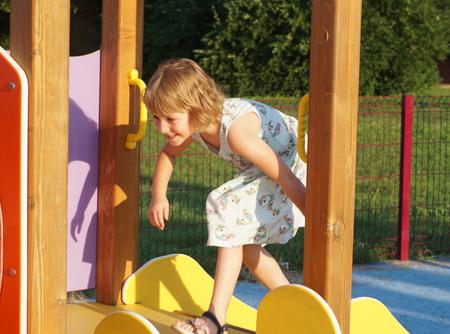 Une petite fille sur une aire de jeux. Activités de développement de l'enfant sur une aire de jeux pour enfants