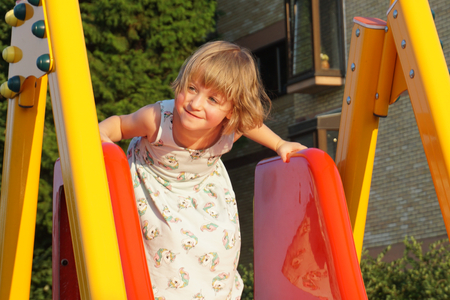 Cute and happy little girl on the toboggan on the children playground in the sunny summer day