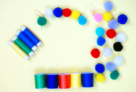 Sewing accessories in different colors, threads, needle and pompons, flat lay