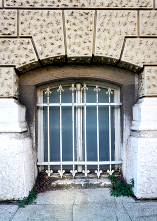 Old ruined secession window with decorative metal grids