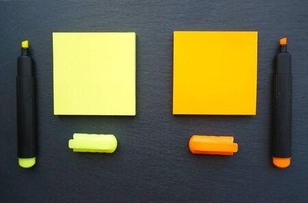 Two sticky notes in yellow and orange color with marker pens in the same color on the black board background flat lay
