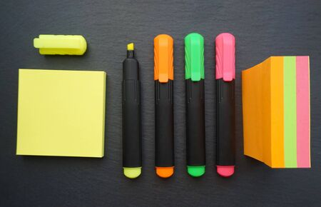 Multicolored neon marker pens or fine liner in the various colors on the black board background with post note stickers block paper by the side Stock Photo - 129732895