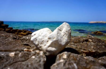 White heart shaped stone in front of the beautiful blue sea and sky horizon line. Beautiful summer love background with copy space