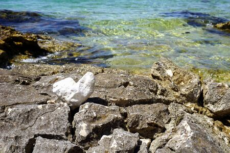 Heart shaped white pebble on the big rocks by the sea coast in front of the blue sea surface