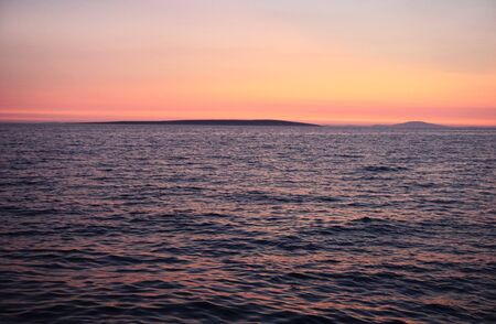 Vivid color horizon on a wavy sea surface and skyline on the summer sunset