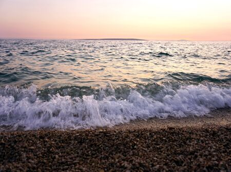 Tidal waves and sea foam on the seashore and pebble beach at sunset on the beautiful seascape